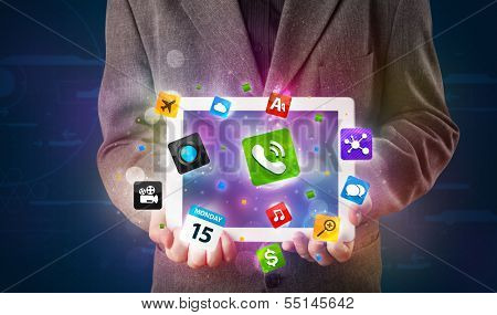Young businessman holding a tablet with modern colorful apps and icons