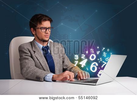 Handsome young man sitting at desk and typing on laptop with 3d numbers comming out