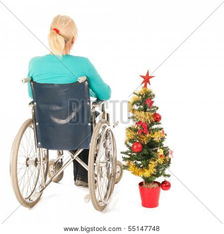 Blond woman in wheel chair with Christmas tree isolated over white background