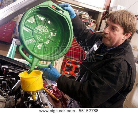 Automotive Technician Auto Mechanic Refills Radiator After Service