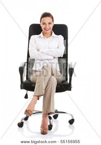 Beautiful happy business woman sitting on a chair. Isolated on white.