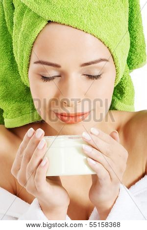 Beautiful woman in bathrobe and turban smelling body lotion. Isolated on white.