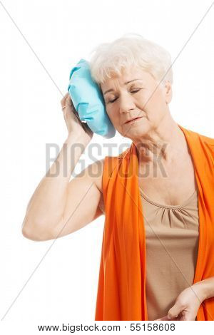 An old lady with ice bag by her head. Isolated on white.