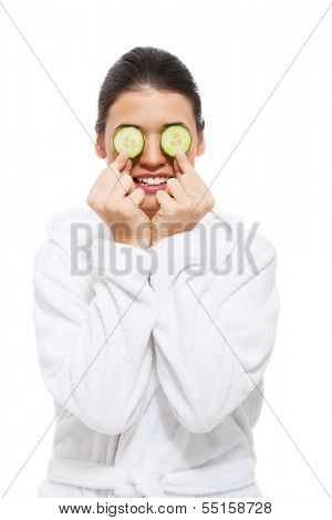 beautiful young woman in bathrobe with cucumber on eyes. isolated on white.