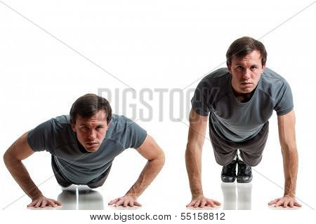 Young adult man doing push ups. Studio shot over white.