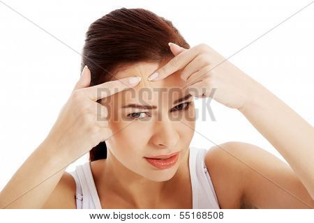 Young woman is pimpling spot on forehead. Isolated on white.