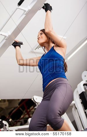 Strong woman doing bar pull ups
