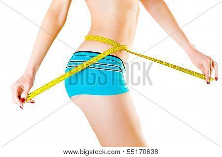 Slim young woman measuring waist