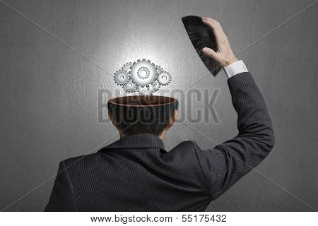 Working Metal Gears Inside Businessman Head In Gray Concrete Wall Background