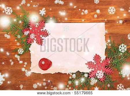 Frame with vintage paper and Christmas decorations on wooden background