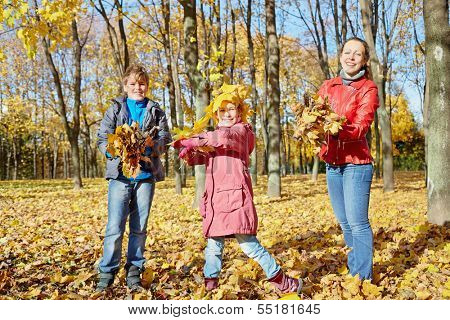 Mother and two children play with yellow fallen leaves in autumn park