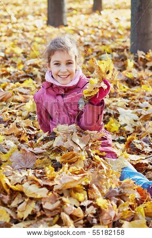 Smiling little girl in red jacket sits in drift of maple fallen yellow leaves in autumn park