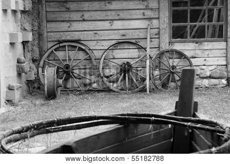 Old wooden wheels of cart at a barn wall.