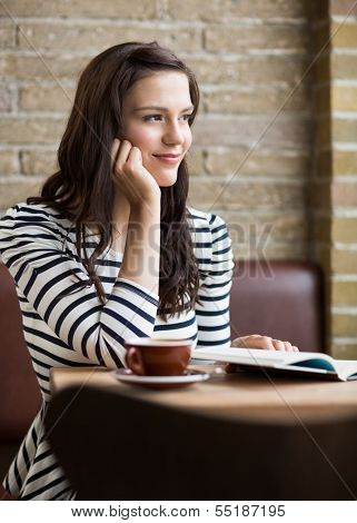 Thoughtful young woman with hand on chin looking away in coffeeshop