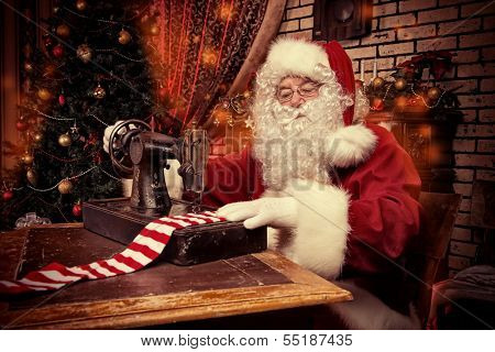 Santa Claus is sewing on a sewing machine striped socks for Christmas.