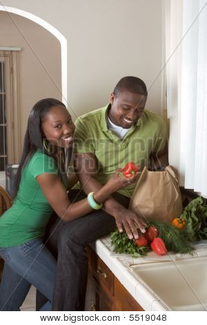 Young Ethnic Couple On Kitchen Sorting Groceries