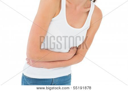 Close-up mid section of a casual woman with stomach pain over white background