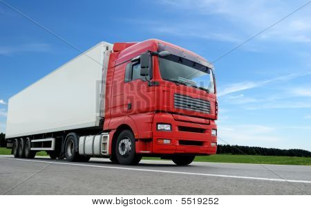 Red Lorry With White Trailer Over Blue Sky