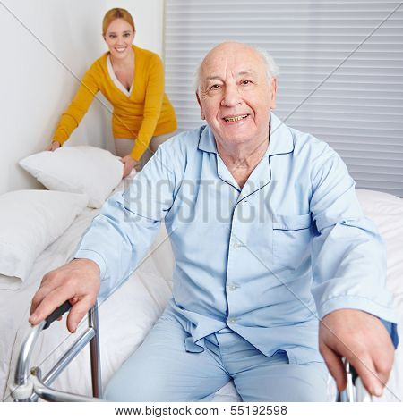 Woman fixing sheets of bed for senior citizen man in the family