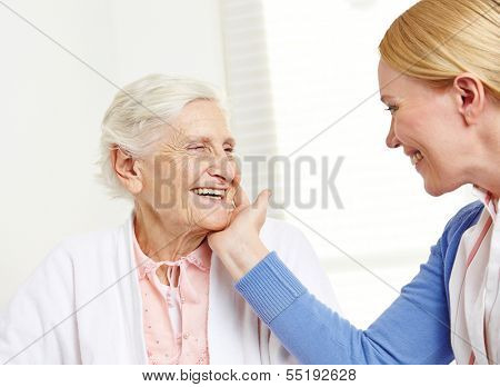 Daughter caressing happy senior mother with her hand over her cheek