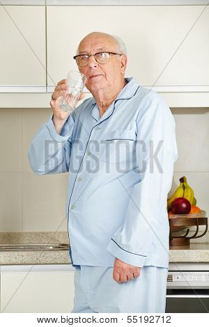 Senior man in his pajamas drinking a glass of water in the kitchen