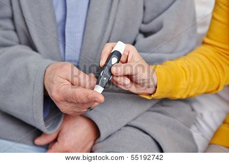 Hand of senior man with diabetes getting blood glucose monitoring