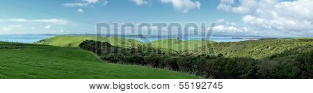 Panoramic View Over Rolling Hills In Front Of The Sea