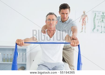 Male therapist massaging mans shoulder in the hospital