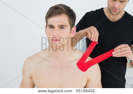Male physiotherapist putting on red kinesio tape on patients shoulder in the medical office