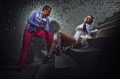stock photo of basement  - Stylish pimp and his bride women dark basement - JPG