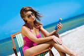 picture of suntanning  - A young woman in a swimsuit adding suntan on the beach - JPG