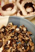 pic of champignons  - Closeup of sliced diced and spiced champignon mushrooms in a ceramic bowl in the foreground next to a bowl of raw toadstools of champignons in the background selective oicus
