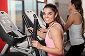 picture of elliptical  - Beautiful young brunette working out in an elliptical trainer and smiling - JPG