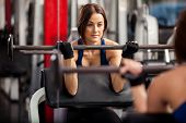 picture of barbell  - Pretty young woman lifting a barbell in front of a mirror at the gym - JPG