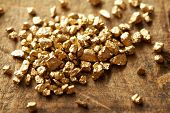 picture of gold nugget  - Mound of gold on a old wooden work table - JPG