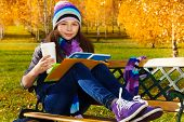 image of 11 year old  - Portrait of nice smiling 11 years old girl holding coffee mug and textbook wearing blue purple hat and scurf