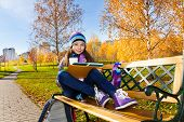 image of 11 year old  - Nice happy smiling 11 years old girl holding coffee mug and textbook wearing blue purple hat and scurf sitting on the bench in the park
