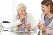 Happy senior woman playing cards with eldercare nurse