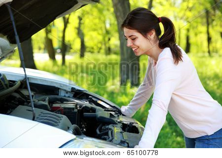 Happy woman looks under hood car background green park