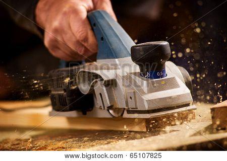 Elderly Man Planing A Plank Of Wood