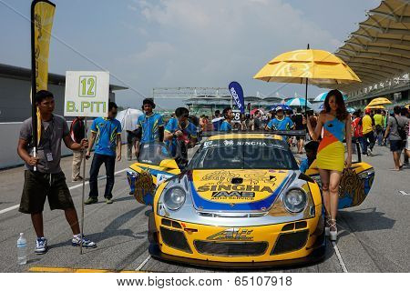 SEPANG, MALAYSIA - MAY 11, 2014: The Singha Porsche AAS Team grid girl poses with the team car, a Porsche 997 at the start grid of the Thailand Supercar Race in Sepang International Circuit.