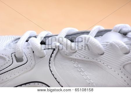 Closeup of laces on a brand new sneaker. The athletic shoe is all white as are the laces, horizontal format on a wood floor.