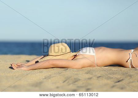 Woman Resting Sunbathing On The Sand Of The Beach With A Picture Hat