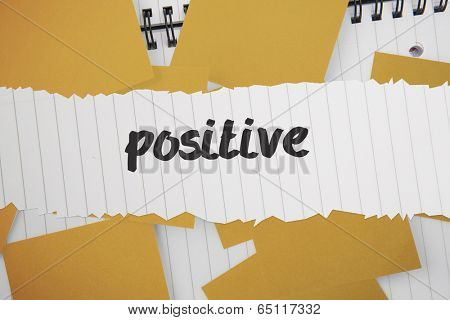 The word positive against yellow paper strewn over notepad