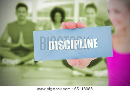 Fit blonde holding card saying discipline against yoga class in gym