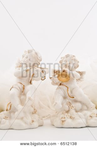 Figurines In The Form Of The Angels Playing Musical Instruments