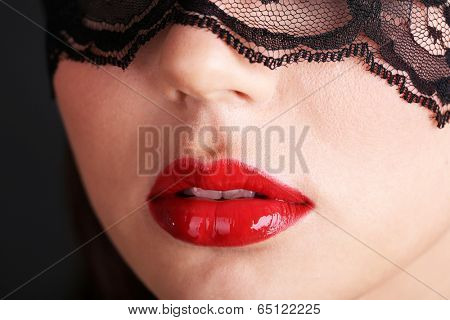 Girl with red lips and openwork black eye shades on dark background