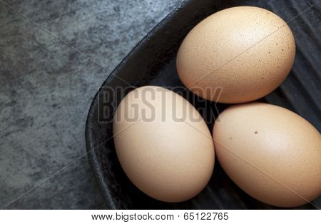 Three brown eggs in cast iron skillet.