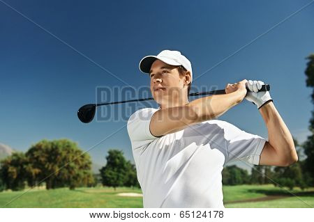 Golfer hitting driver club on course for tee shot