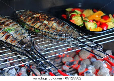 Grilled Fresh Fish (Trout) on the barbecue next to a pan of Fried vegetables